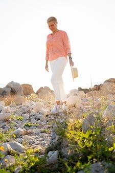 Retrato completo de mulher caminhando sobre pedras