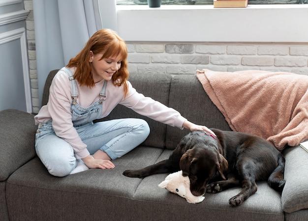 Retrato completo de mulher e cachorro no sofá