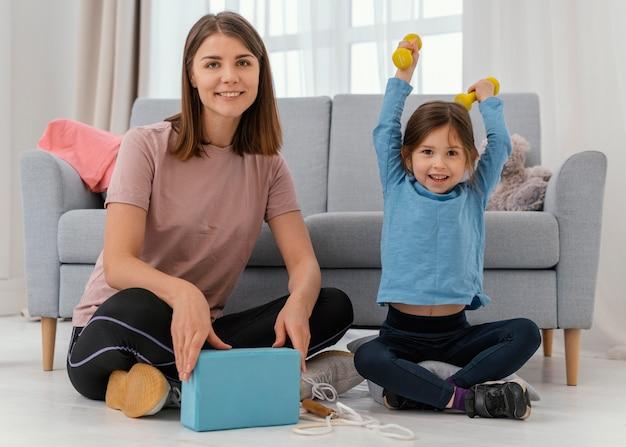Retrato completo de mulher e menina dentro de casa