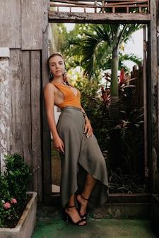 Retrato completo de mulher elegante e estilosa usando acessórios na cabeça e saia longa e salto alto posando em um parque exótico