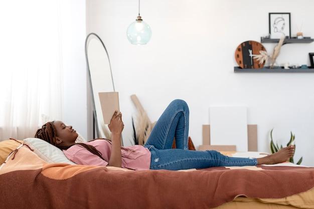 Retrato completo de mulher lendo na cama