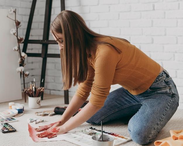 Retrato completo de mulher pintando com as mãos