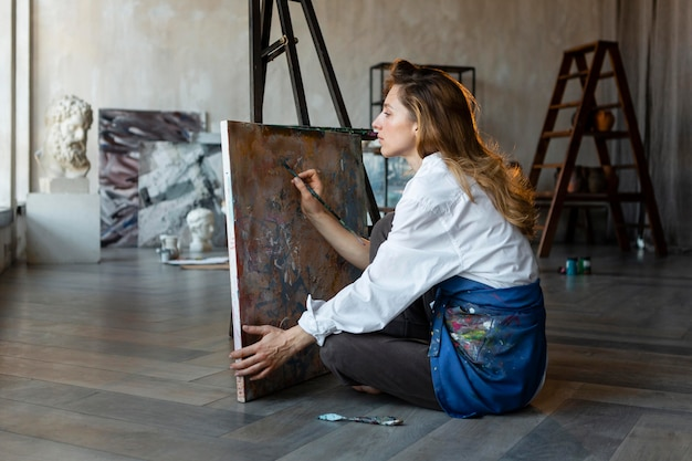 Retrato completo de mulher pintando em tela