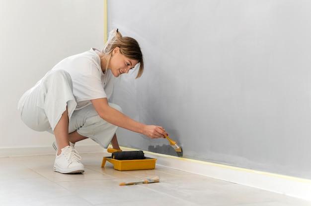 Retrato completo de mulher pintando parede