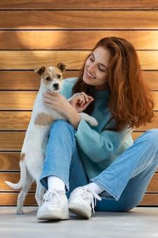 Retrato completo de mulher posando com um cachorro fofo
