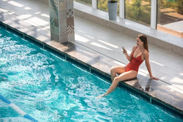 Retrato completo de mulher segurando o telefone