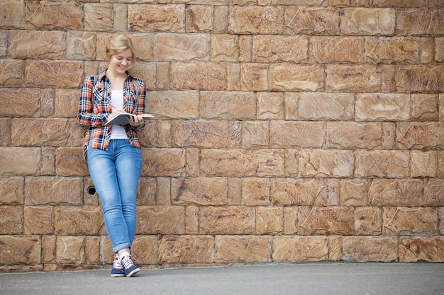 Retrato completo de uma estudante contra a parede de tijolos