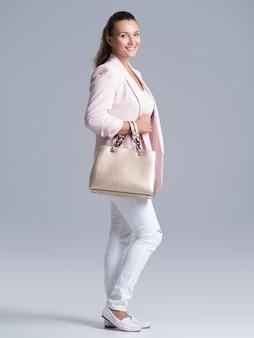 Retrato completo de uma jovem mulher feliz com bolsa posando no estúdio.