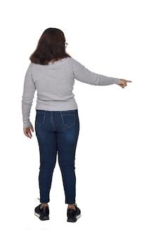 Retrato completo de uma mulher apontando o dedo para a frente, isolado no branco