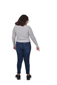 Retrato completo de uma mulher apontando o dedo para baixo, isolado no branco