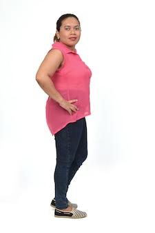 Retrato completo de uma mulher em pé e vista lateral, olhando para a câmera em um fundo branco, com as mãos no quadril