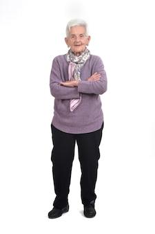 Retrato completo de uma mulher idosa com os braços cruzados sobre um fundo branco