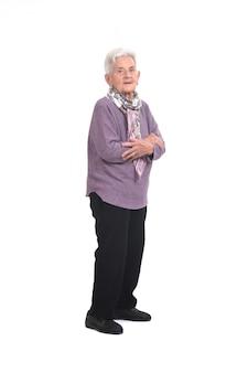 Retrato completo de uma mulher idosa, vista lateral, braços cruzados e olhando para a câmera em fundo branco