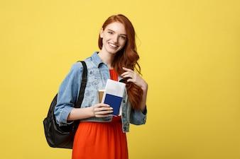 Retrato completo do estúdio do comprimento da mulher consideravelmente nova do estudante que guarda o passaporte com bilhetes.