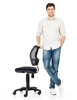 Retrato completo do homem feliz sorridente fica perto da cadeira isolada no branco.