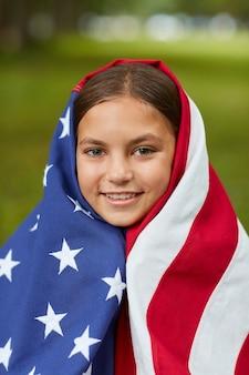 Retrato completo vertical de uma linda garota coberta pela bandeira americana, sorrindo enquanto está sentado na grama verde ao ar livre