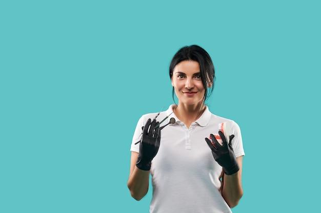 Retrato confiante de um jovem dentista alegre com mandíbula gessada e utensílios odontológicos nas mãos, olhando para a câmera enquanto posava contra um fundo azul