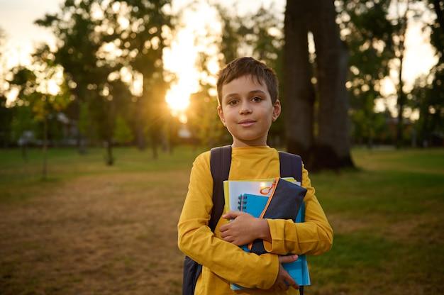 Retrato confiante de um menino de 9 anos de idade com uma mochila segurando pastas de trabalho e um estojo de lápis nas mãos e um sorriso fofo posando para a câmera no contexto da natureza ao pôr do sol