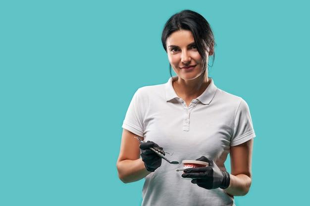 Retrato confiante de uma médica dentista em uniforme médico com utensílios odontológicos e mandíbula posando olhando para a câmera isolada em um fundo azul