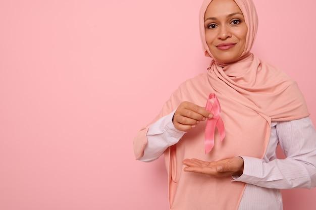 Retrato confiante de uma mulher muçulmana de meia-idade usando um hijab segurando uma fita de cetim rosa na altura do peito para mostrar seu apoio aos pacientes com câncer e sobreviventes. dia mundial da conscientização do câncer de mama.