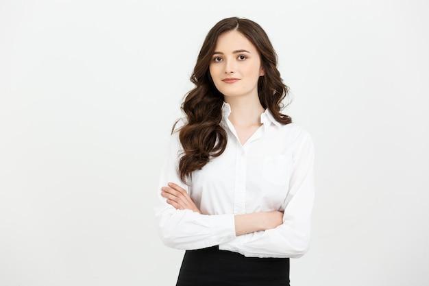 Retrato confiante jovem empresária mantendo os braços cruzados e olhando para a câmera