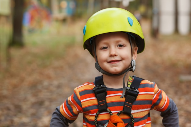 Retrato corajoso garotinho se divertindo no parque de aventura