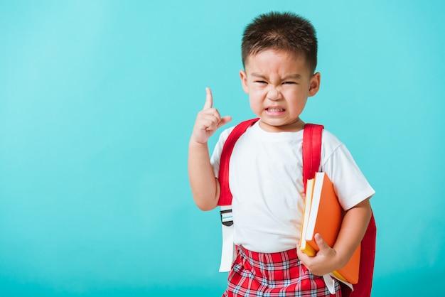 Retrato criança asiática menino rosto sério abraçando livros pensando e aponte o dedo no espaço