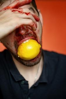 Retrato criativo de um homem com um limão em um fundo vermelho