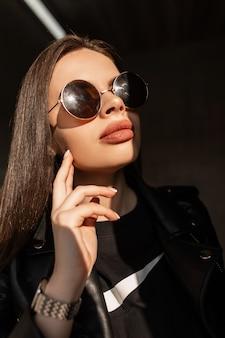 Retrato criativo elegante de uma jovem mulher com rosto de beleza natural e lábios grandes em roupas da moda pretas e óculos de sol redondos vintage fica na luz do sol e na sombra em um fundo escuro