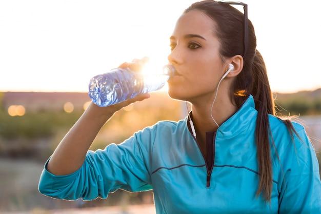 Retrato da água bebendo da mulher nova após o corredor.