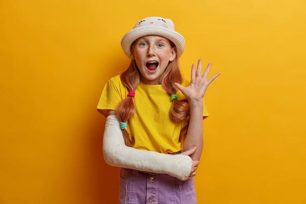 Retrato da alegre garota ruiva acena a palma da mão em um gesto de olá, diz oi para os pais, estando de bom humor, usa roupa de verão, elenco no braço quebrado após cair durante patins, isolado na parede amarela