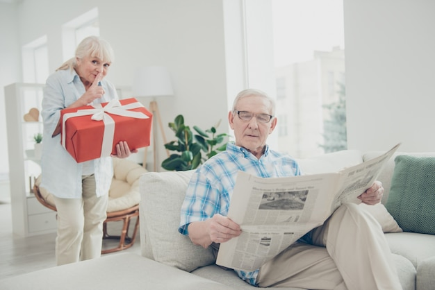 Retrato da avó de pessoas adoráveis carregando um grande presente romântico para o vovô em uma casa com interior branco claro