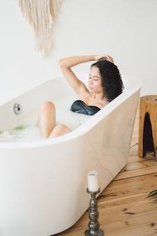 Retrato da bela dama no quarto vazio, tomando banho de leite e pensando segurando o cabelo dela