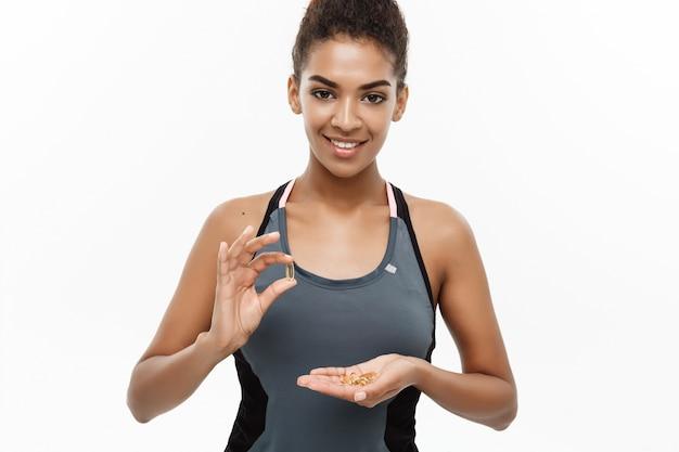 Retrato da bela e feliz mulher afro-americana tomando uma pílula.