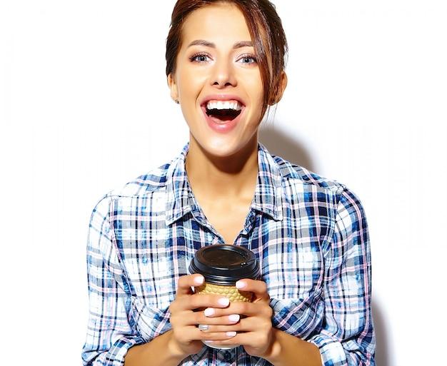 Retrato da bela elegante legal engraçado mulher adolescente enlouquecendo de camisa quadriculada, segurando o copo de café de plástico