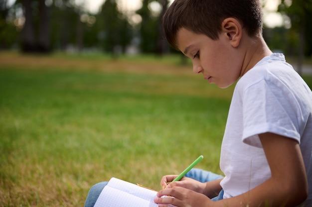 Retrato da bela estudante inteligente com idade elementar, estudante inteligente fazendo lição de casa, resolvendo tarefas de matemática, aproveitando o estudo ao ar livre. volta às aulas, conhecimento, educação, conceitos de erudição
