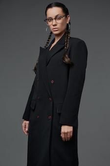 Retrato da bela garota hispânica encantadora no casaco preto comprido