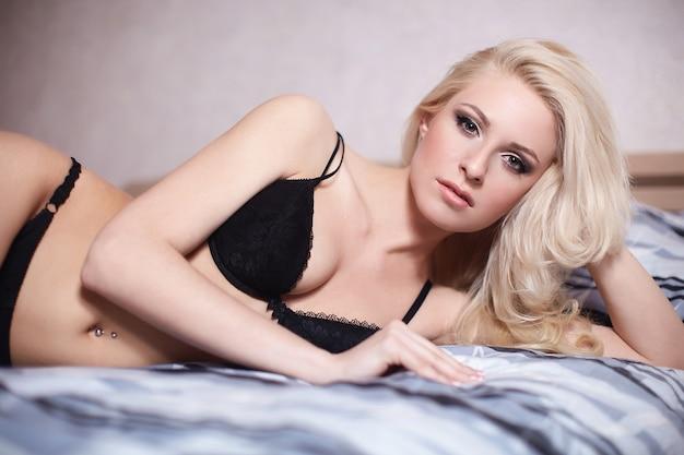 Retrato da bela garota loira sexy, deitada na cama em lingerie preta com penteado e maquiagem brilhante