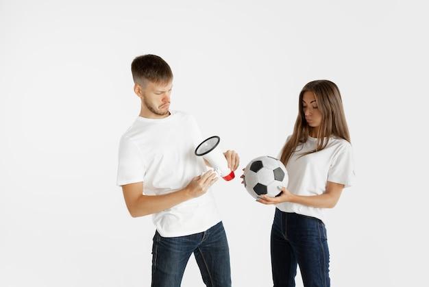 Retrato da bela jovem casal futebol ou fãs de futebol em fundo branco do estúdio. expressão facial, emoções humanas, publicidade, conceito de esporte. mulher e homem pulando, gritando, se divertindo.