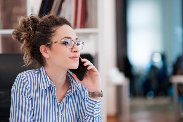 Retrato da bela jovem empresária com óculos sentado no local de trabalho e falando no celular