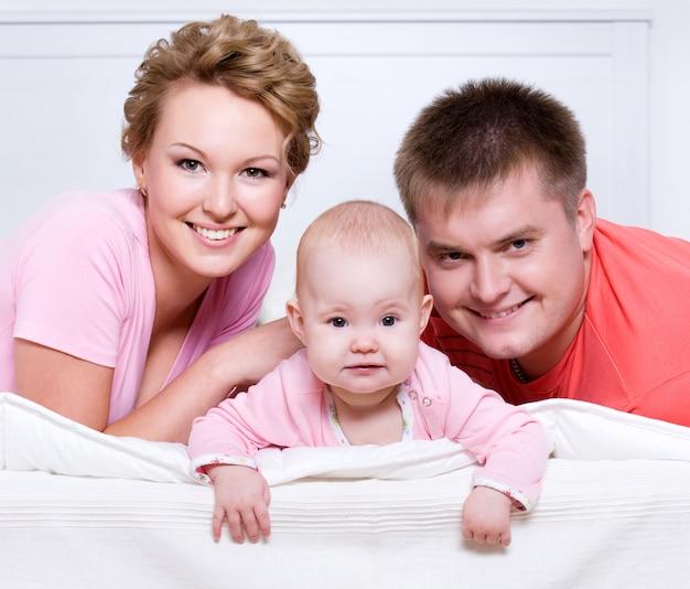 Retrato da bela jovem família feliz deitada na cama em casa