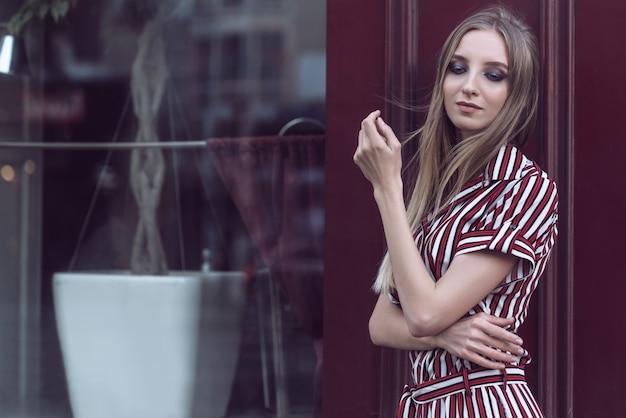 Retrato da bela jovem modelo com cabelo comprido e maquiagem brilhante com um café de rua no fundo