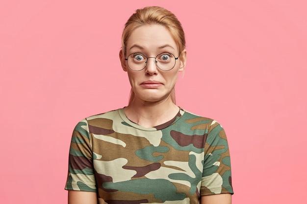 Retrato da bela jovem modelo feminina branca em pé sobre um fundo rosa, tem expressão chocada, não acredita no sucesso, vê algo inacreditável.