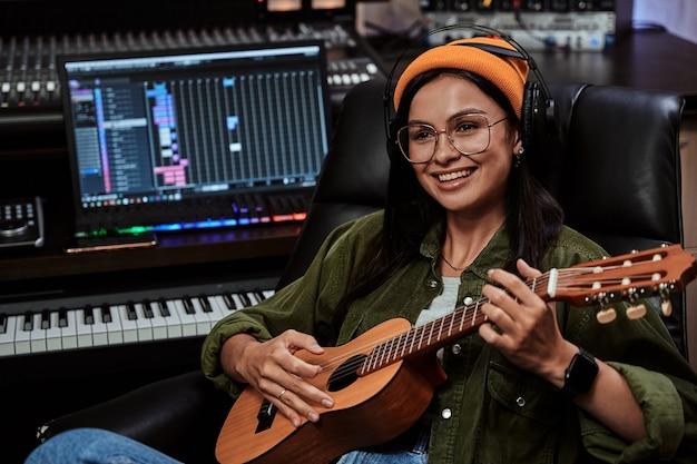 Retrato da bela jovem morena artista feminina sentada no estúdio de gravação e tocando cavaquinho