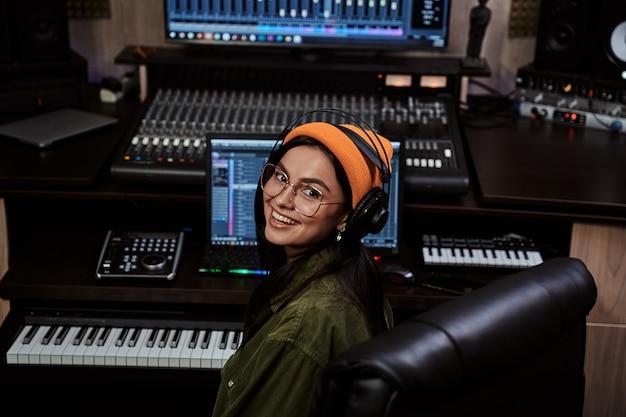 Retrato da bela jovem morena artista feminina sorrindo para a câmera enquanto tocava o teclado