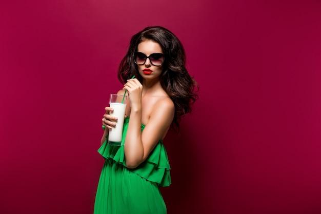 Retrato da bela jovem morena de óculos escuros e vestido verde com coquetel
