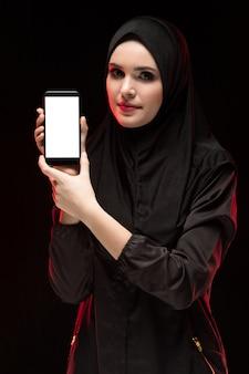 Retrato da bela jovem muçulmana inteligente vestindo preto hijab celular publicidade nas mãos dela como preto conceito de educação