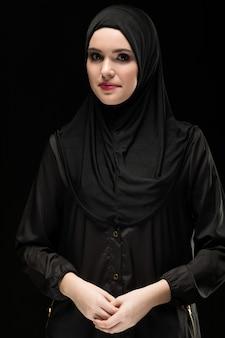 Retrato da bela jovem muçulmana positiva vestindo preto hijab como conceito de moda conservadora com a mão na mão, sorrindo em fundo preto