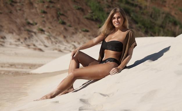 Retrato da bela jovem sexy na areia moída na luz do sol ao ar livre