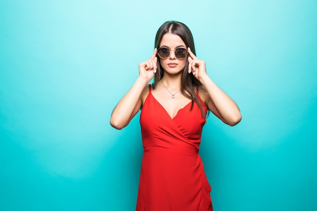 Retrato da bela jovem vestida de vermelho na parede azul